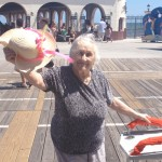 Rita Nolfi waving her hat on the boardwalk.